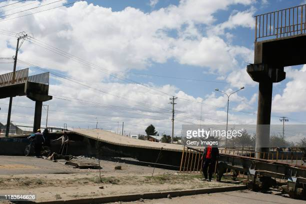 Supporters of Evo Morales stand next to a fallen bridge during a blockade to the road to the Senkata Fuel Plant on November 20 2019 in El Alto...