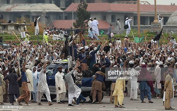 Supporters of executed Islamist Mumtaz Qadri shout slogans as they watch security forces helicopters during an antigovernment protest front the...