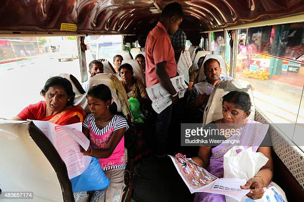 Supporters of exTamil rebel carders hand out election campaign leaflets to voters on a bus during campaigning in the remote village of Nelliady on...