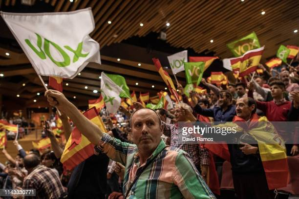 Supporters of far right wing party VOX wave Spanish and VOX flags as they attend a rally at Palacios de Congresos on April 17 2019 in Granada Spain...