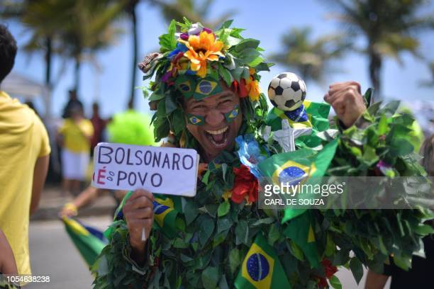 TOPSHOT Supporters of farright lawmaker and presidential candidate for the Social Liberal Party Jair Bolsonaro are pictured in Rio de Janeiro Brazil...
