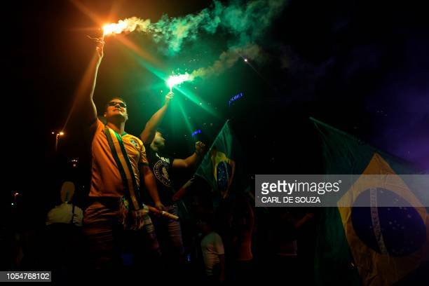 Supporters of farright lawmaker and presidential candidate for the Social Liberal Party Jair Bolsonaro celebrate in Rio de Janeiro after the former...