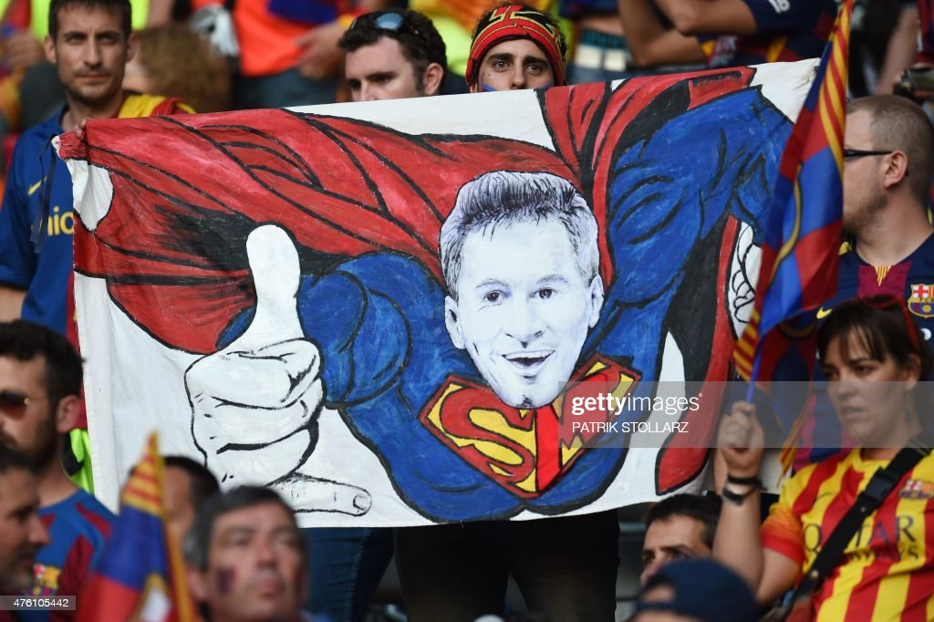 Supporters of FC Barcelona hold up a poster of Barcelona's Argentinian forward Lionel Messi as Superman prior to the UEFA Champions League Final football match between Juventus and FC Barcelona at the Olympic Stadium in Berlin on June 6, 2015.