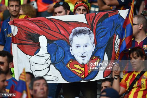 Supporters of FC Barcelona hold up a poster of Barcelona's Argentinian forward Lionel Messi as Superman prior to the UEFA Champions League Final...