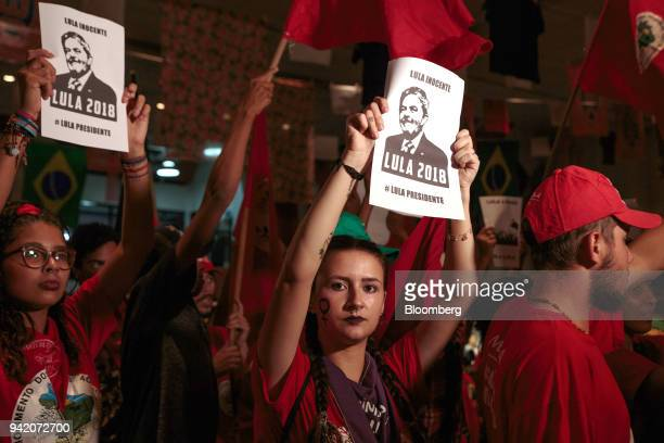 Supporters of former Brazilian President Luiz Inacio Lula da Silva hold signs during the Supreme Court's sentence ruling at the Metal Worker's Union...