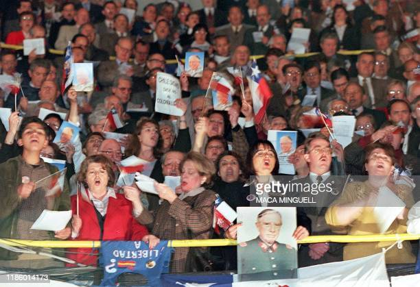 Supporters of former Chilean dictator Gen Augusto Pinochet wave portraits of their hero along with national flags while gathered in a local theater...