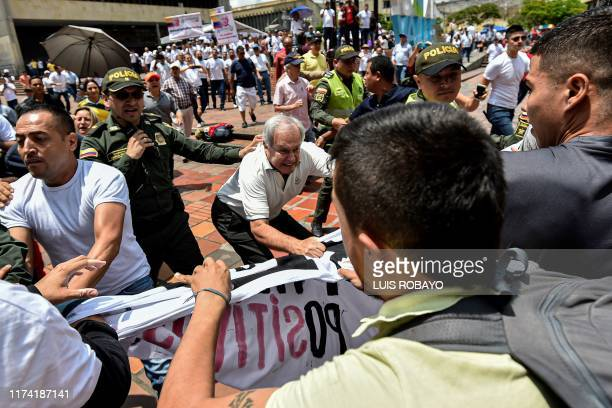 Supporters of former Colombian President Alvaro Uribe confront opponents with a sign against him during a rally in his support as police try to...
