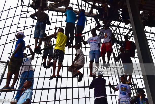 TOPSHOT Supporters of former international Liberian football star turned politician George Weah climb on a fence as they attend a presidential...