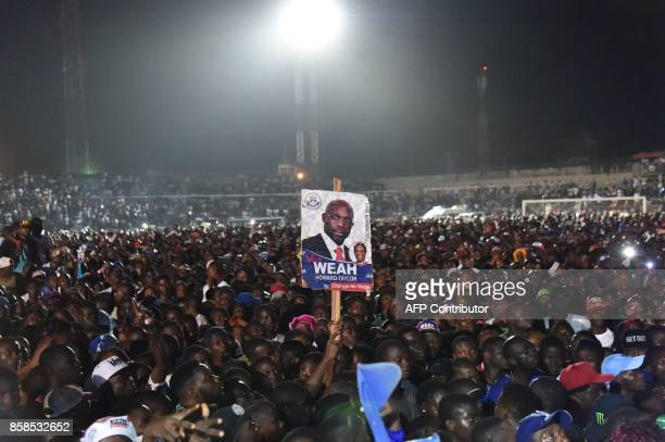 TOPSHOT Supporters of former international Liberian football star turned politician George Weah hold up his poster as they attend a presidential...