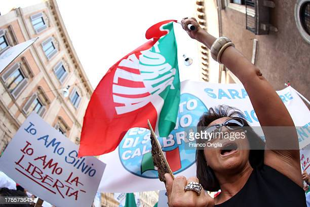 Supporters of former Italian Prime Minister Silvio Berlusconi hold banners and flags aloft as they attend a rally organised by the People of Freedom...