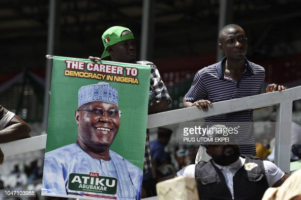 Supporters of former Nigerian vicePresident Atiku Abubakar hold a poster as they celebrate his winning of the presidential ticket of the opposition...