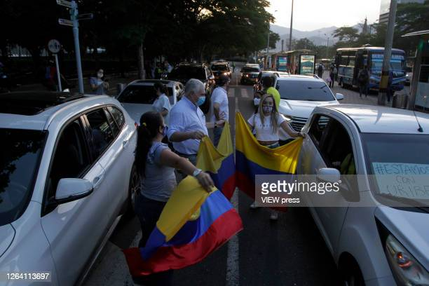 Supporters of former President and Senator Alvaro Uribe Velez wearing protective masks show colombian flags during a protest against the Supreme...