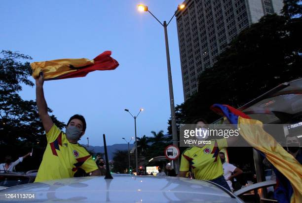 Supporters of former President and Senator Alvaro Uribe Velez wearing protective masks wave colombian flags during a protest against the Supreme...