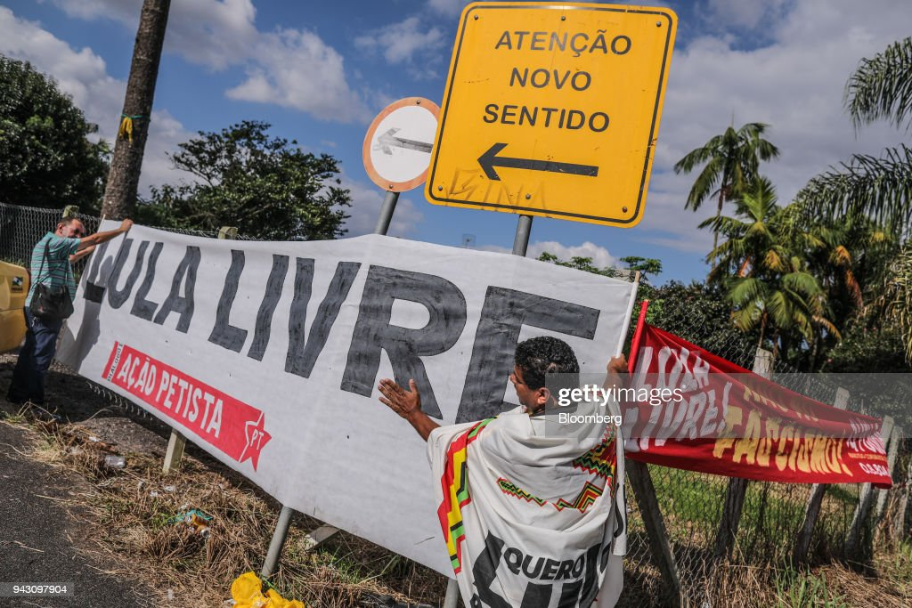 Supporters of former President Luiz Incio Lula da Silva hold a banner that reads 'Free Lula,' while waiting Federal Police headquarters in Curitiba, Brazil, on Saturday, April 7, 2018. Lula said he will turn himself in to police, finally ending a tense stand-off with the authorities after he ignored a court-ordered deadline to begin a prison sentence. Photographer: Andre Coelho/Bloomberg via Getty Images