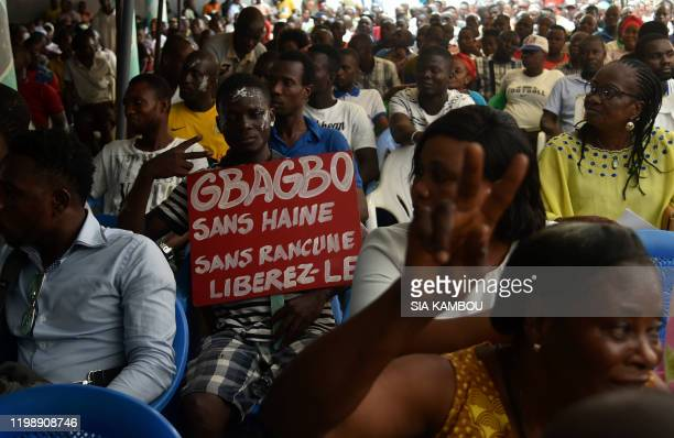 Supporters of former President of Ivory Coast Laurent Gbagbo hold up a sign that reads Gbagbo no hate no grudge free him while following proceedings...