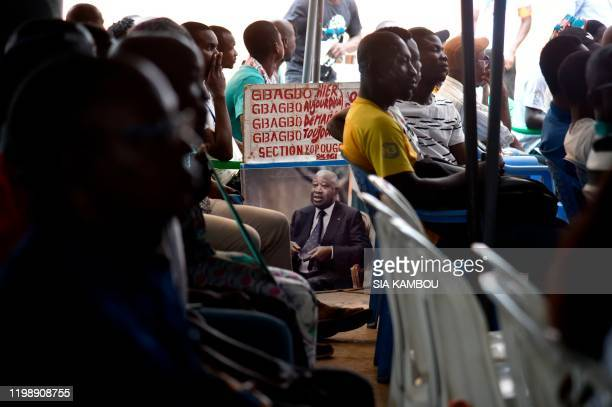 Supporters of former President of Ivory Coast Laurent Gbagbo hold up a sign while following proceedings of the International Criminal Court trial of...