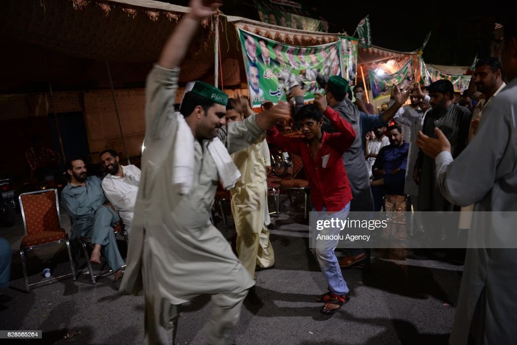 Supporters of former Prime Minister of Pakistan Nawaz Sharif dance before his speech during a rally in Rawalpindi Pakistan on August 10 2017...