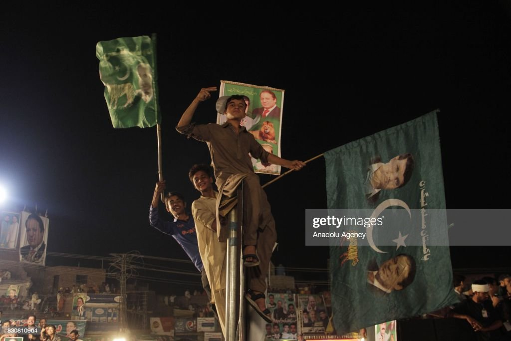Supporters of former Prime Minister of Pakistan Nawaz Sharif stand on pole during rally in Lahore Pakistan on August 12 2017