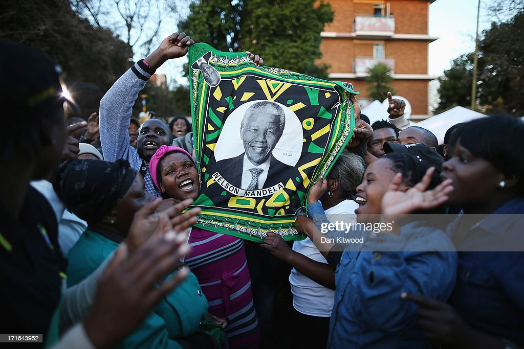 Supporters of former South African President Nelson Mandela hold a flag depicting the former South African leader as they wait to hear news of his condition outside the Heart Hospital where Mandela is being treated for a lung infection June 27, 2013 in Pretoria, South Africa. Family members and President Jacob Zuma visited Mandela during his 20th day in the hospital.