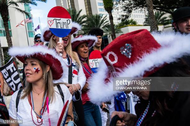 Supporters of former US President Donald Trump cheer for his arrival outside of a hotel where the Conservative Political Action Conference 2021 is...