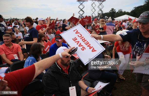 """Supporters of former U.S. President Donald Trump pass out pre-approved placards during a """"Save America"""" rally at York Family Farms on August 21, 2021..."""