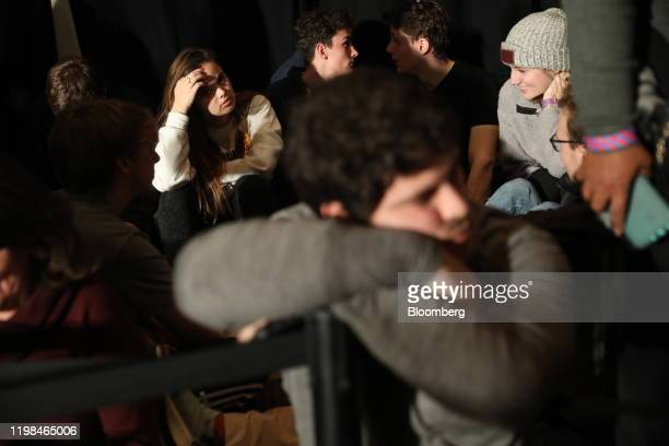 Supporters of former US Vice President Joe Biden 2020 Democratic presidential candidate wait for results during a caucus night watch party in Des...