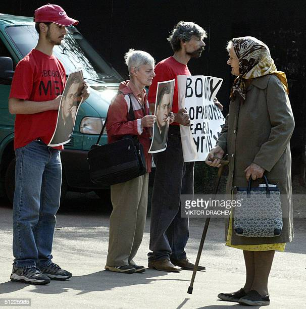 Supporters of former Yukos chief Mikhail Khodorkovsky hold posters with his picture as an old woman looks at them near the court house during the...