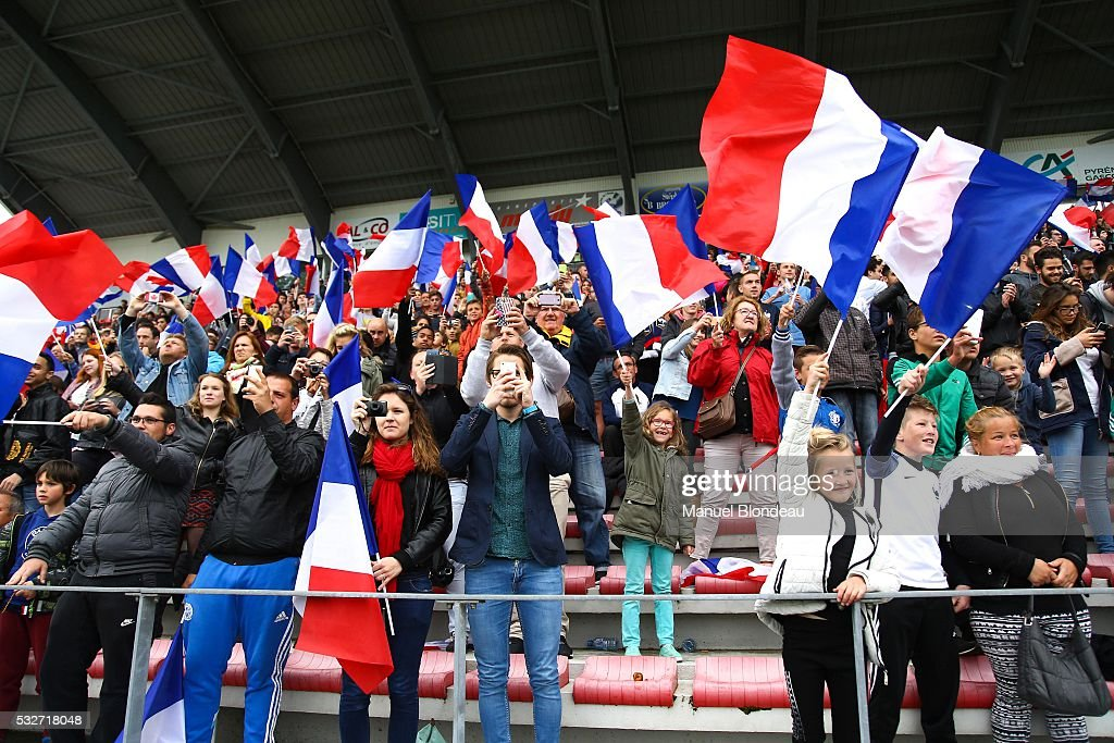 Supporters of France wave flags during a training session during the preparation on the French football Team for Euro 2016 on May 19, 2016 in Biarritz, France.