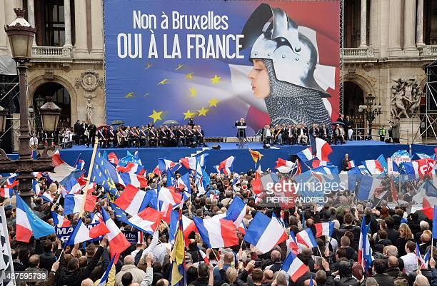 Supporters of France's farright National Front wave French flags as leader Marine Le Pen delivers a speech in front of a poster depicting Joan of Arc...