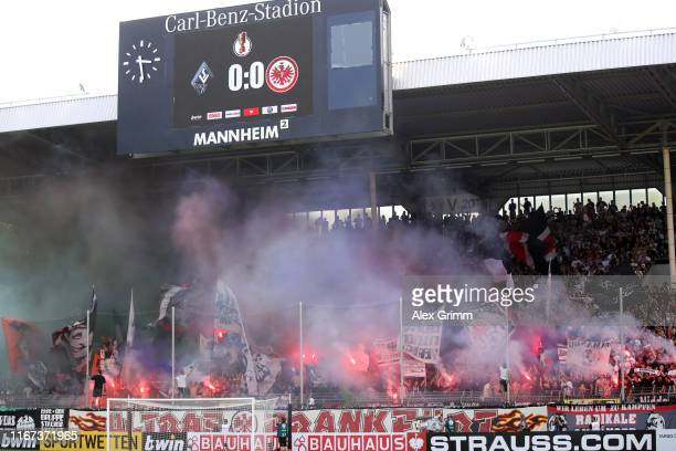Supporters of Frankfurt burn flares prior to the DFB Cup first round match between SV Waldhof Mannheim and Eintracht Frankfurt at Carl-Benz-Stadion...