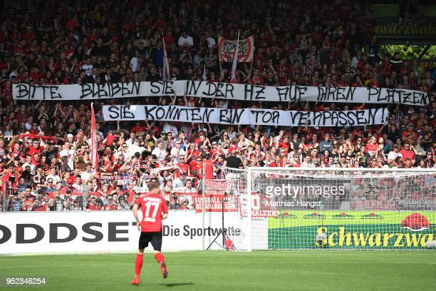 Supporters of Freiburg display a banner reminding everyone to stay seated during half time as they could miss a goal during the Bundesliga match...