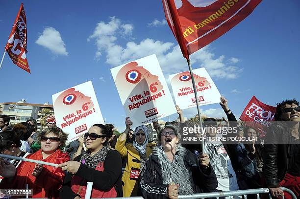 Supporters of French Front de Gauche leftist party's candidate for the 2012 French presidential election wave placards during a campaign meeting on...