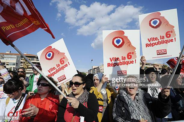 Supporters of French Front de Gauche leftist party's candidate for the 2012 French presidential election hold banners during a campaign meeting on...