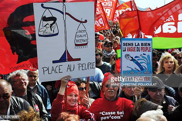 Supporters of French Front de Gauche leftist party's candidate for the 2012 French presidential election hold placards during a campaign meeting on...