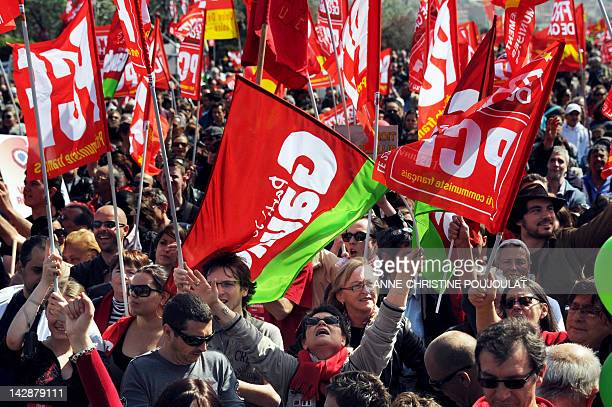 Supporters of French Front de Gauche leftist party's candidate for the 2012 French presidential election hold flags during a campaign meeting on...
