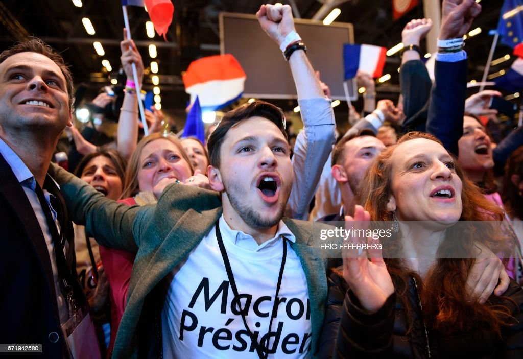 TOPSHOT - Supporters of French presidential election candidate for the En Marche ! movement celebrate after the results of the first round of the presidential election, on April 23, 2017 at the Parc des Expositions in Paris. Centrist Emmanuel Macron and far-right leader Marine Le Pen will contest the second round of the French presidential election, initial projections suggested on April 23, after a nailbiting vote seen as vital for the future of the EU. / AFP PHOTO / Eric FEFERBERG