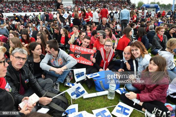 Supporters of French third division football club 'Les Herbiers' gather at the stadium in Les Herbiers western France on May 8 to watch on a giant...