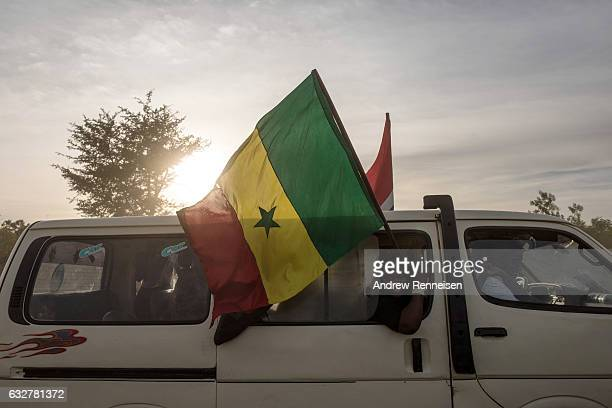 Supporters of Gambian President Adama Barrow waves a flag as the president leaves Banjul International Airport on January 26, 2017 in Banjul, The...