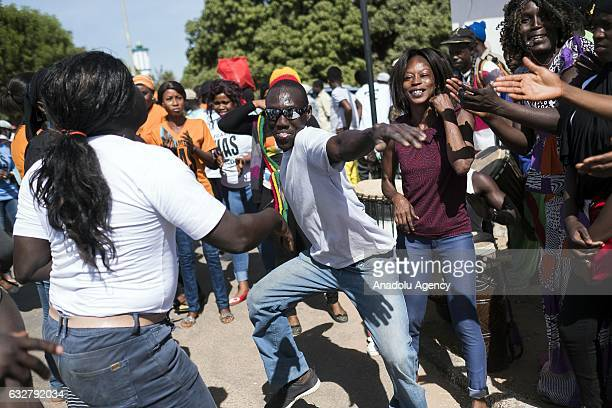 Supporters of Gambia's president Adama Barrow celebrate as they wait for the arrival of him at Banjul International Airport aftermath of his...