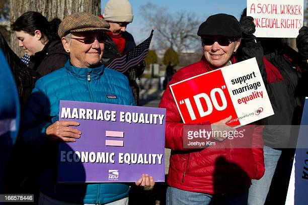 Supporters of gay marriage hold signs during the DOMA and Prop 8 hearing at the Supreme Court in March 2013.