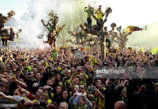 Supporters of German soccer champions Borussia Dortmund celebrate their team during a parade through the streets of Dortmund, western Germany, on May...