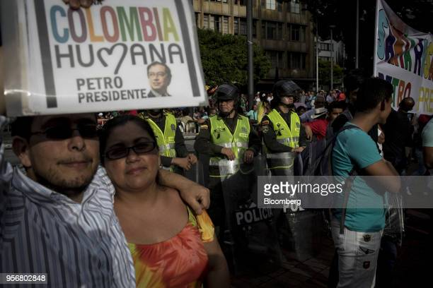 Supporters of Gustavo Petro presidential candidate for the Progressivists Movement Party hold up signs as police watch over a campaign rally in...