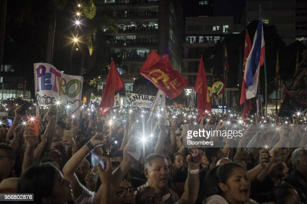 Supporters of Gustavo Petro presidential candidate for the Progressivists Movement Party hold up illuminated smartphones and flags during a campaign...