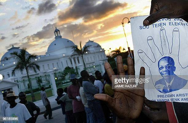 Supporters of Haitian President Jean Bertrand Aristide show a proAristide pamphlet as hundreds gather on a street in front of the presidential palace...