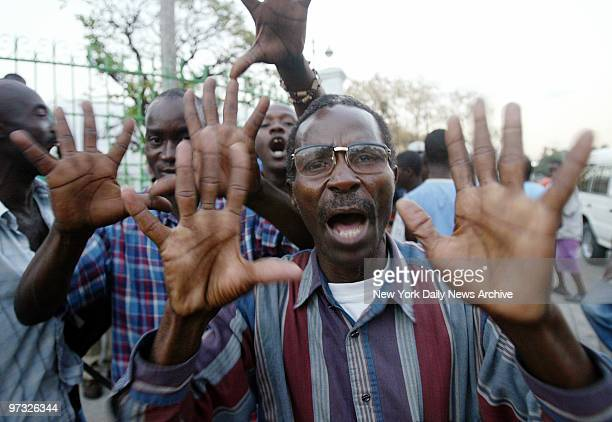Supporters of Haitian President Jean-Bertrand Aristide in Port-au-Prince hold up five fingers representing the five years remaining in his...