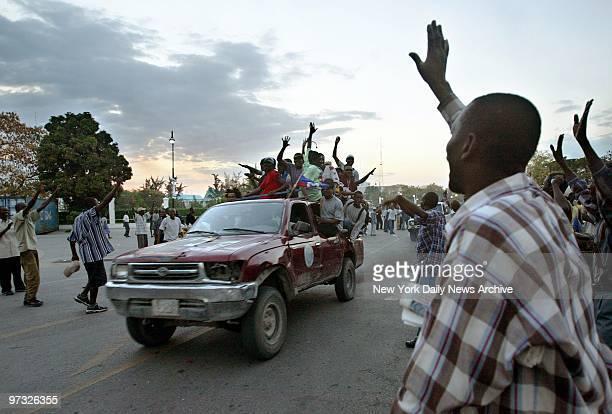 Supporters of Haitian President Jean-Bertrand Aristide wave to a truck filled with fellow supporters in front of the National Palace in...