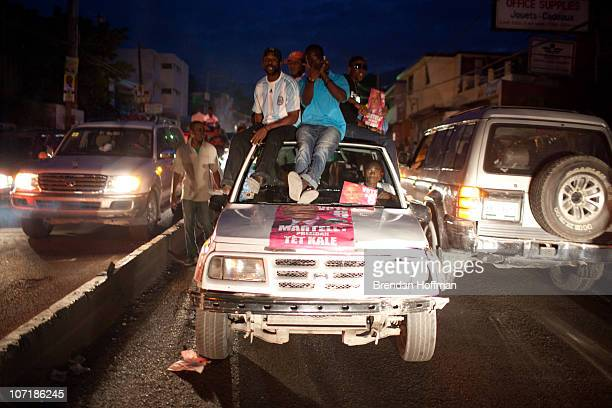 Supporters of Haitian presidential candidate Michel Martelly ride on top of a truck during an impromptu election protest on November 28 2010 in...