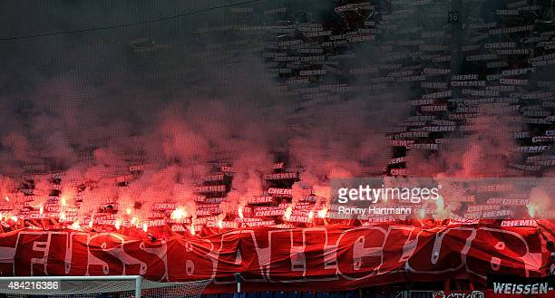 Supporters of Halle handle with pyro technics during the Third League match between 1 FC Magdeburg and Hallescher FC at MDCCArena on August 16 2015...