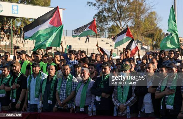 Supporters of Hamas wave flags during a rally in Gaza City on May 24, 2021. - A ceasefire was reached late last week after 11 days of deadly violence...