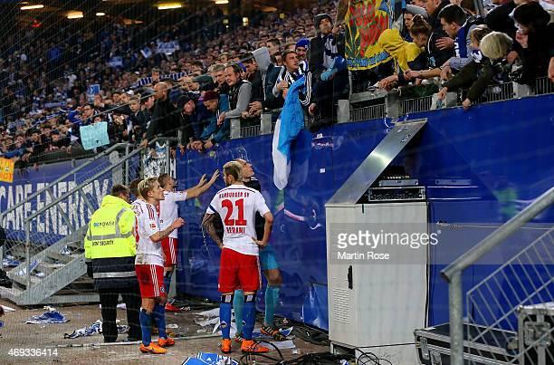 Supporters of Hamburg argue with Rene Adler Heiko Westermann and Valon Behrami of Hamburg after the Bundesliga match between Hamburger SV and VfL...